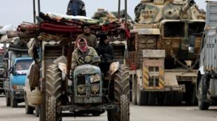 Des Syriens déplacés à l'intérieur de la campagne ouest d'Alep passent devant des véhicules militaires turcs à Hazano près d'Idleb, le 11 février 2020.