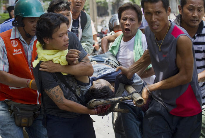 Anti-government Red Shirt protesters carry the body of a man who was shot dead