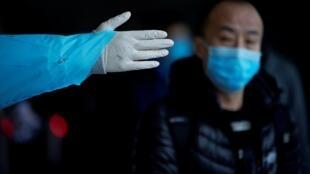 Un passager portant un masque sort de la gare à Shanghai, en Chine, alors que le pays est frappé par une épidémie de coronavirus, le 8 février 2020.