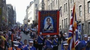 Nacionalistas britânicos exibem a foto da rainha Elizabeth II pelas ruas de Edimburgo.