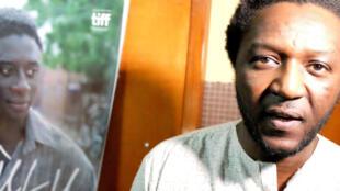 Le réalisateur malien Daouda Coulibaly. Sur l'affiche de « Wulu », l'acteur Ibrahim Koma qui incarne Ladji.