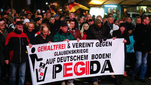 Des participants à la manifestation anti-immigration et  contre l'islamisation, organisée par le mouvement Pegida, tiennent une banderole à Dresde, le 15 décembre 2014.