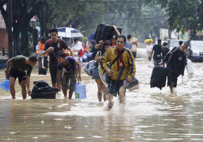 Moradores de Manila deixam suas casas após enchentes que atingiram a capital filipina.