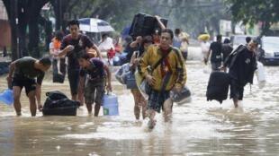 Moradores de Manila deixam suas casas após enchentes provocadas pelo tufão Haiyan.