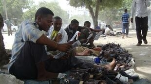 Men in Mogadishu sit beside their shoe business as they read newspapers to keep up to date on the 2010 World Cup
