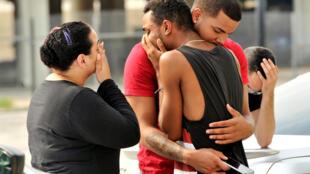 Amigos e parentes das vítimas choram em frente à delegacia