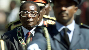 Zimbabwe President Robert Mugabe inspects troops at the opening of Parliament July 20, 2000.