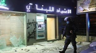 Policial faz ronda diante de agência bancária atacada durante protestos em Beirute.