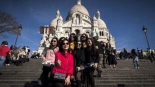 Des touristes se prennent en photo devant la basilique du Sacré-Coeur à Paris.