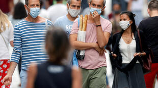 People wearing protective masks walk in the Montorgueil street in Paris as France reinforces mask-wearing all over the country.