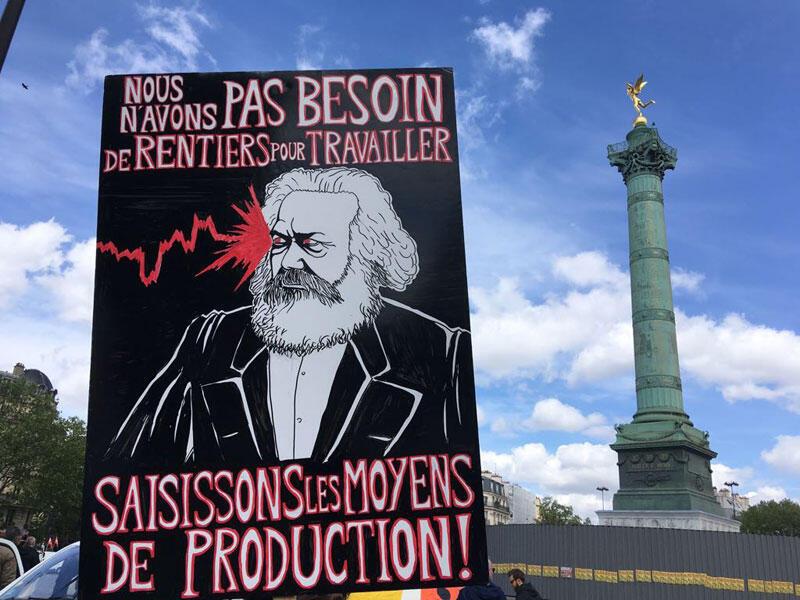 """1 мая 2018 г. в Париже: плакат с надписью """"Нам не нужны рантье, чтобы работать. Захватим средства производства"""""""