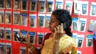 Une vendeuse indienne de téléphones portables en communication qui recharge un autre portable alors que l'OMS vient de déclarer que l'usage excessif du téléphone portable pourrait être cancérogène. Photo le 2 juin 2011.