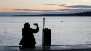 Une femme assise à côté de sa valise, le long du lac Léman, prend une photo avec son portable alors que le soleil se lève le 21 août 2017, à Genève.