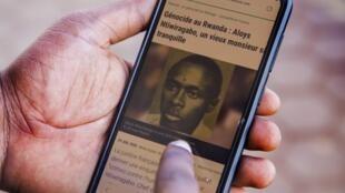 Un Rwandais lit un article de TV5 sur Aloys Ntiwiragabo.