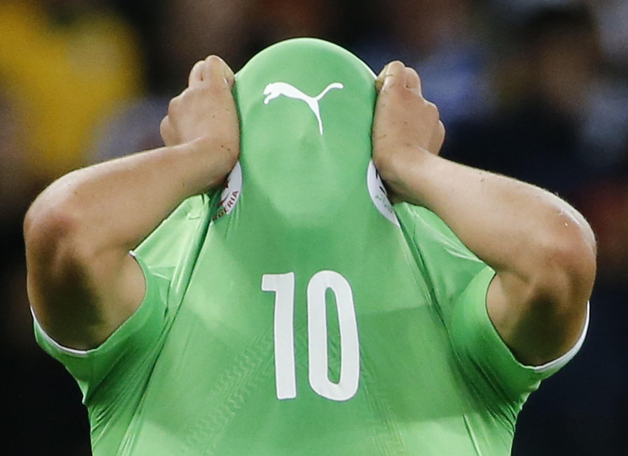 Algeria's Sofiane Feghouli covers his face as he reacts to his team's loss against Germany, Porto Alegre, 30 June 2014.