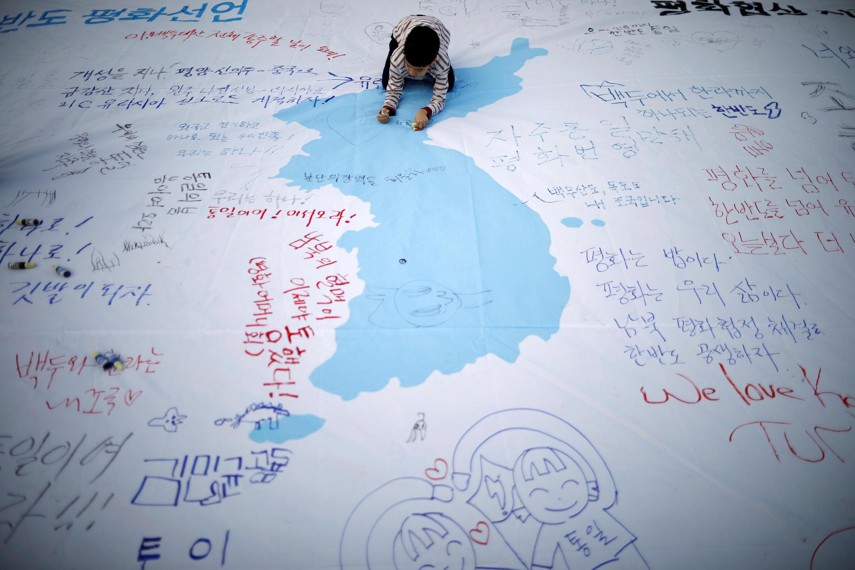 Một em bé viết lời chúc Thượng Đỉnh Liên Triều thành công tốt đẹp bên trên một bản đồ Triều Tiên thống nhất. Ảnh chụp tại Seoul, ngày 21/04/2018.