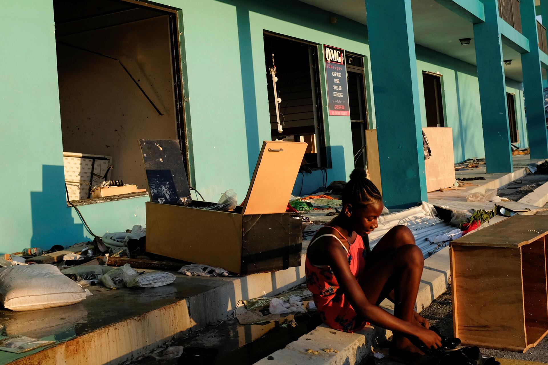 Une femme essaye des chaussures devant un magasin pillé après que l'ouragan Dorian ait frappé les îles Abaco à Marsh Harbour, aux Bahamas, le 5 septembre 2019.