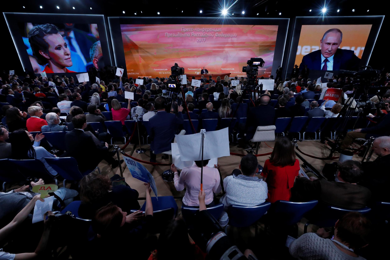 Tổng thống Nga Vladimir Putin phát biểu tại cuộc họp báo thường niên ở Mátxcơva (Nga) ngày 15/12/2017. Bà Ksenia Sobchak, thuộc phe đối lập lắng nghe.