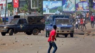 Mmoja wa waandamanaji akikabiliana na vikosi vya usalama, Oktoba 24 huko Conakry (picha ya kumbukumbu).