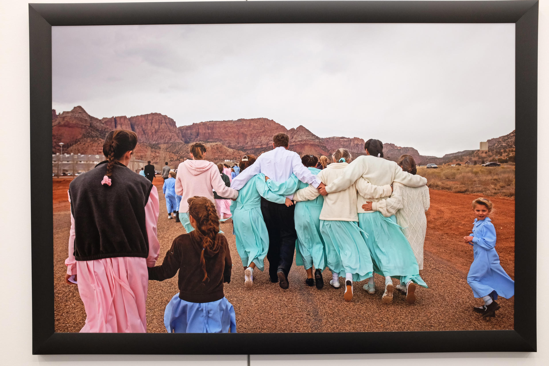 « Un fidèle de l'Eglise des saints des derniers jours (FSDJ) sort d'un enterrement avec six de ses épouses. » Vue de la photographie de Stephanie Sinclair, exposée dans le cadre de « Too Young To Wed », dans l'Arche du photojournalisme.