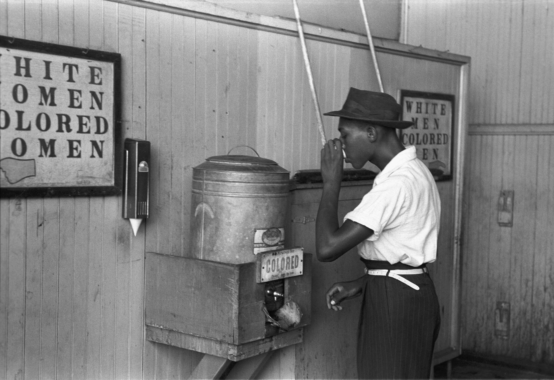 Afroamericano bebiendo en una fuente reservada a las personas de color, en los años 50.