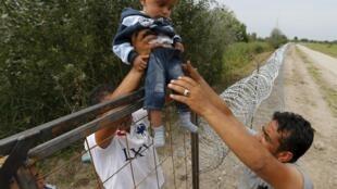 Người tỵ nạn Kurdistan-Syria vượt qua rào chắn chống người nhập cư được dụng lên ở biên giới giữa Serbia và Hungary,  ngày 25/08/2015.
