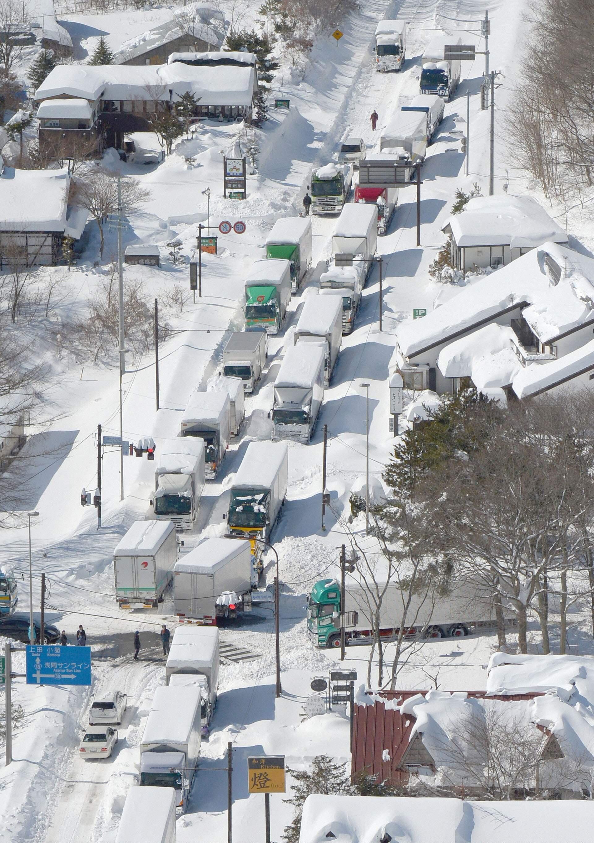 Caminhões estão bloqueados em estrada de Karuizawa, devido à neve neste domingo.