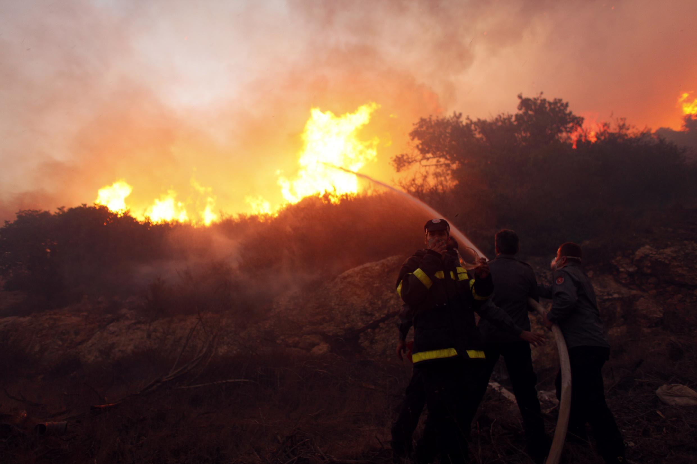 Bombeiros lutam para apagar as chamas do incêndio florestal que já matou 41 pessoas perto de Haifa, no norte de Israel.