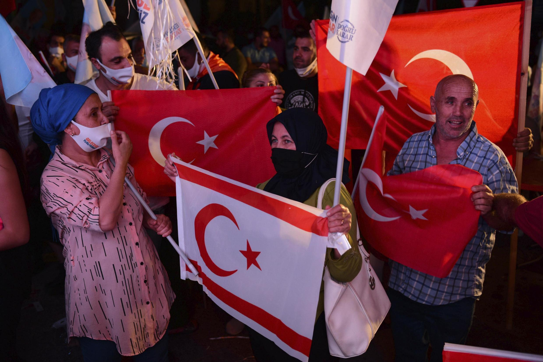 Des Chypriotes tiennent des drapeaux turcs et chypriotes turcs en célébrant la victoire du candidat nationaliste Ersin Tatar, soutenu par la Turquie, à Nicosie, le 18 octobre 2020.
