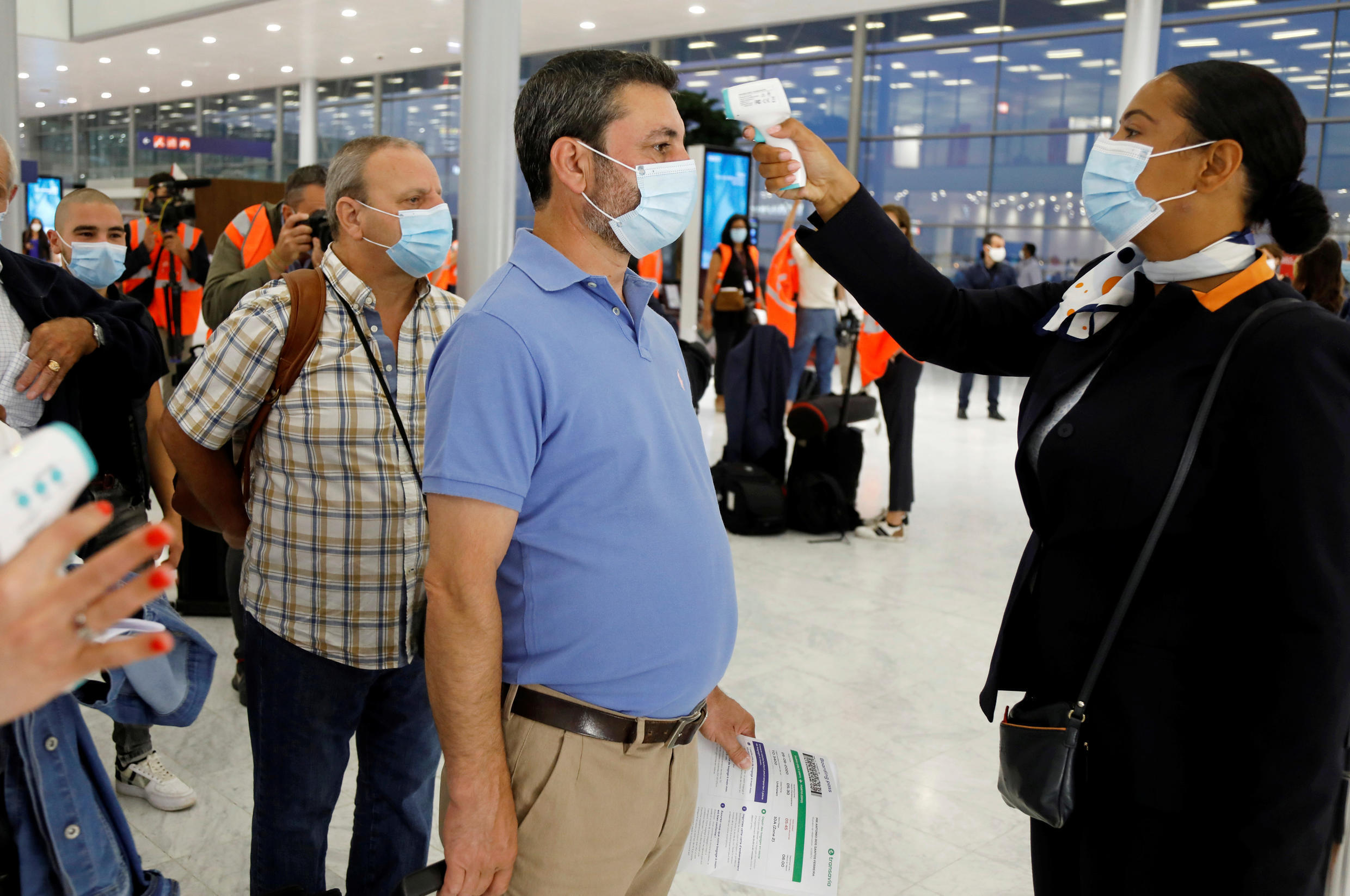 A worker in protective gear sprays disinfectant at Paris-Orly Airport on its re-opening day after shutting due to Covid-19 pandemic,  26 June, 2020.