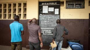 A la gare de Brazzaville, devant le panneau indiquant les horaires des trains pour Pointe-Noire.