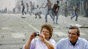 Un couple d'Argentins prend des photos, juste devant l'un des clichés géants d'une exposition consacrée à la crise argentine de 2001, commémorée à Buenos Aires dix ans plus tard en décembre 2011.