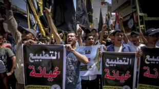 """Manifestantes palestinos sostienen carteles que rezan en árabe """"la normalización es una traición"""" durante una protesta en Gaza el 14 de agosto de 2020"""