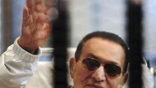 Hosni Mubarak, presidente deposto do Egito, acena para seus apoiadores da sala do tribunal no Cairo, em foto do dia 13 de abril de 2013.