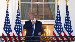 Le président américain de retour à la Maison Blanche après son hopitalisation au centre médical militaire Walter Reed pendant trois jours, retire son masque, le 5 octobre 2020 à Washington.