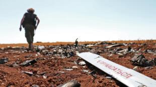 Un combattant rebelle s'approche de ce qui est censé être les restes d'un drone abattu par Israël la veille, dans un champ près de Barqah, à quelques dizaines de kilomètres du Golan occupé par Israël, le 12 juillet 2018.