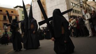Penitente se arrodilla durante una procesión en Malaga, España, este 6 de abril de 2012.
