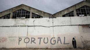 O desemprego em Portugal inspira o grafiti do anjo da morte ao lado do nome do país na porta da fábrica fechada em Lisboa, em imagem desta segunda-feira, 5 de agosto de 2013.