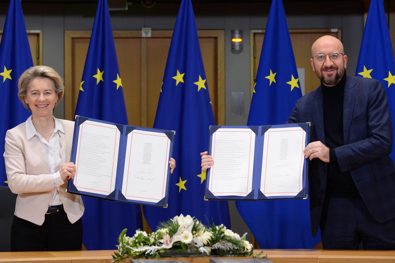 Ursula von der Leyen (izq) y Charles Michel posan con sendas copias del tratado comercial posbrexit con el Reino Unido, el 30 de diciembre de 2020 en Bruselas