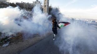 Un manifestant palestinien fuit les gaz lacrymogènes lancés par les forces de l'ordre israéliennes. Ramallah, le 30 novembre 2013.