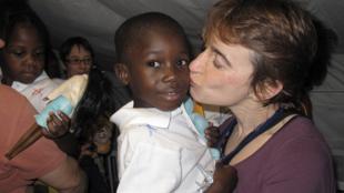 Un enfant haïtien et sa mère adoptive française, le 21 décembre 2010.