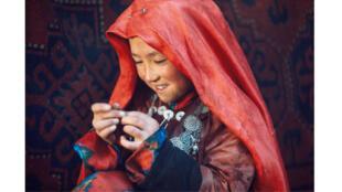 Fillette kirghize occupée à coudre, dans le massif du Pamir.