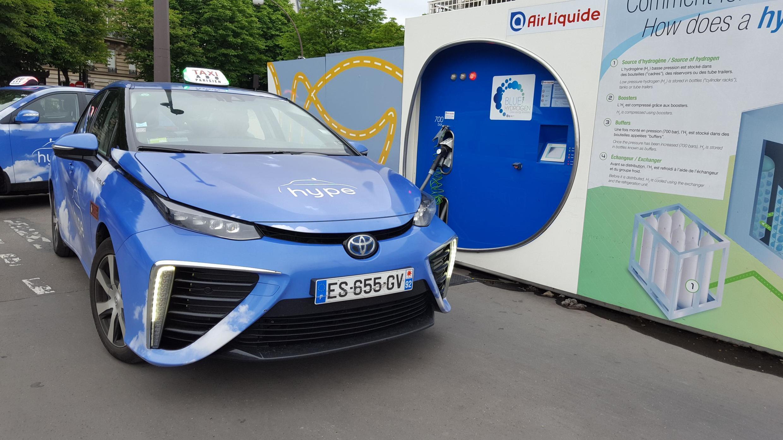 Deux taxis à hydrogène devant l'une des trois stations de la région parisienne, en face de la Tour Eiffel.