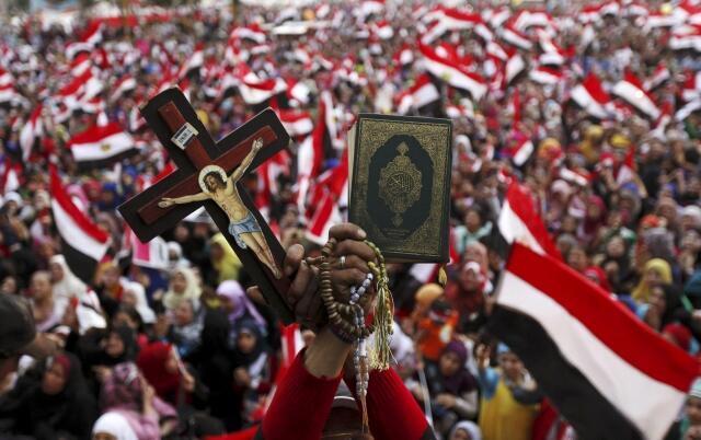 Manifestante segura uma cruz e um exemplar do Corão durante protesto nesta quinta-feira, 4 de julho de 2013, no Cairo.