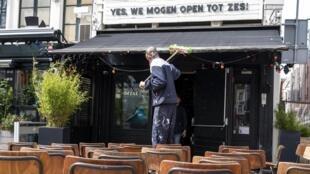 Un empleado limpia una terraza de un café bar en el Amstel, en Amsterdam, el 24 de abril de 2021, luego de que el gabinete holandés decidiera que las terrazas para servicios al aire libre pueden reabrirse a un máximo de 50 clientes debido a la pandemia de Covid-19.
