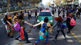 Manifestantes rodean un auto de policía durante la marcha anti sexismo en Santiago de Chile, el 6 de junio de 2018.