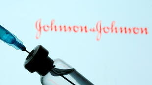 A vial and syringe are seen in front of a displayed Johnson&Johnson logo in this illustration taken January 11, 2021.
