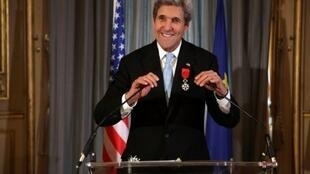 US Secretary of State John Kerry smiles after being awarded the Grand Officier de la Legion d'Honneur (Grand Officer of the Legion of Honor) medal, at the Quai d'Orsay in Paris, on December 10, 2016