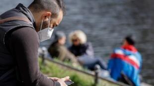 (ARCHIVO) En esta foto de archivo tomada el 2 de abril de 2021, un hombre con una máscara protectora FFP2 mira su teléfono móvil mientras en las orillas del canal Landwehr en el distrito berlinés de Kreuzberg