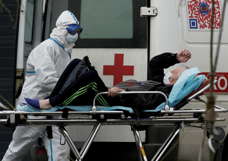 Un médecin spécialement équipé transporte un patient atteint du coronavirus, dans un hôpital de la banlieue de Moscou, le 29 avril 2020.